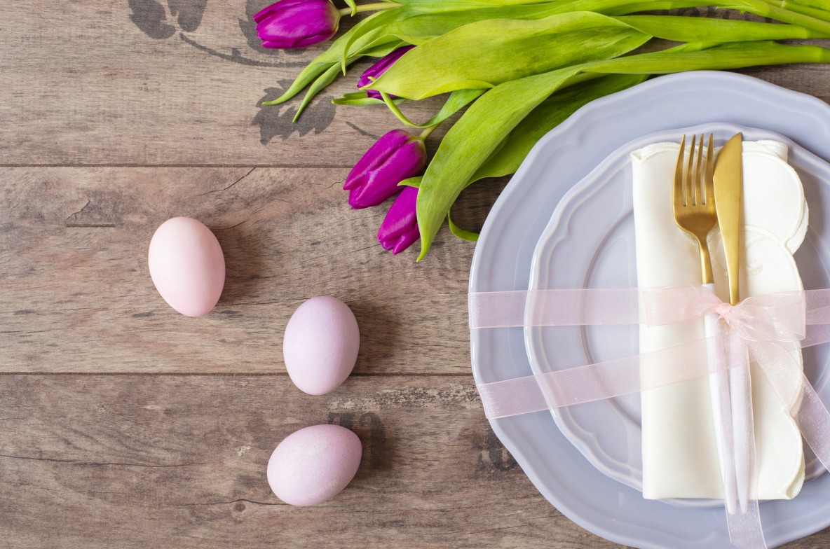 Easter table setting, flatlay with pastel colored Easter eggs, event decoration. Purple dishes and a gold fork and a spoon on a wooden background. Beautiful purple spring tulip flowers