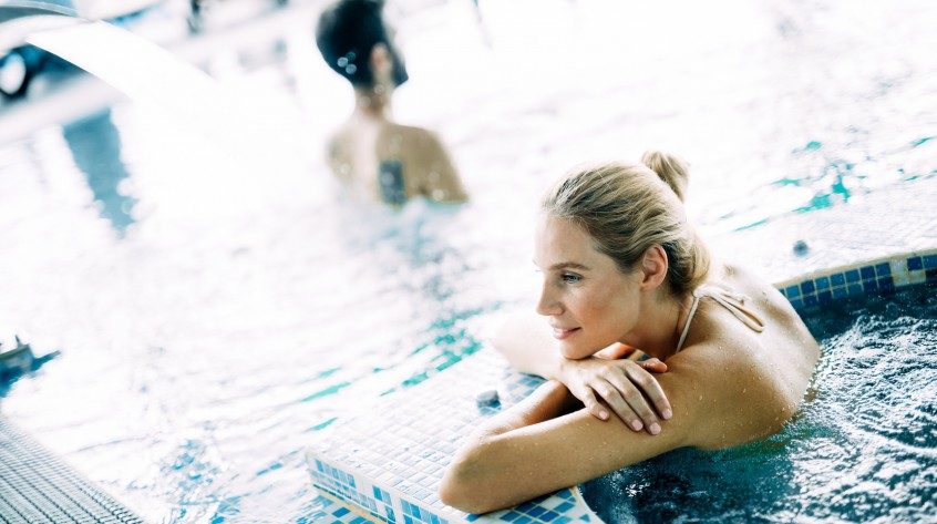 Portrait of beautiful woman relaxing in spa swimming pool